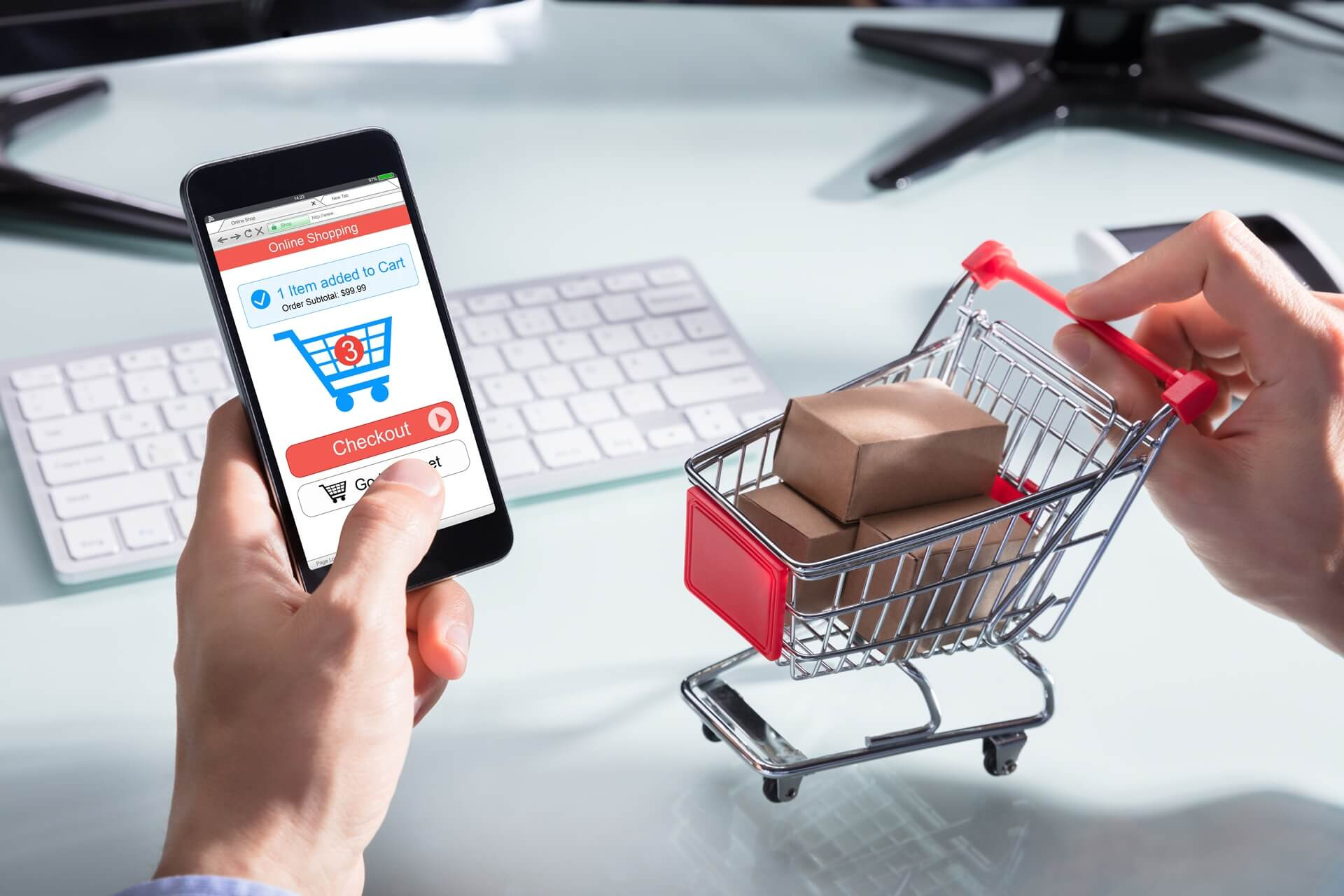 Person holding a miniature shop cart while online shopping