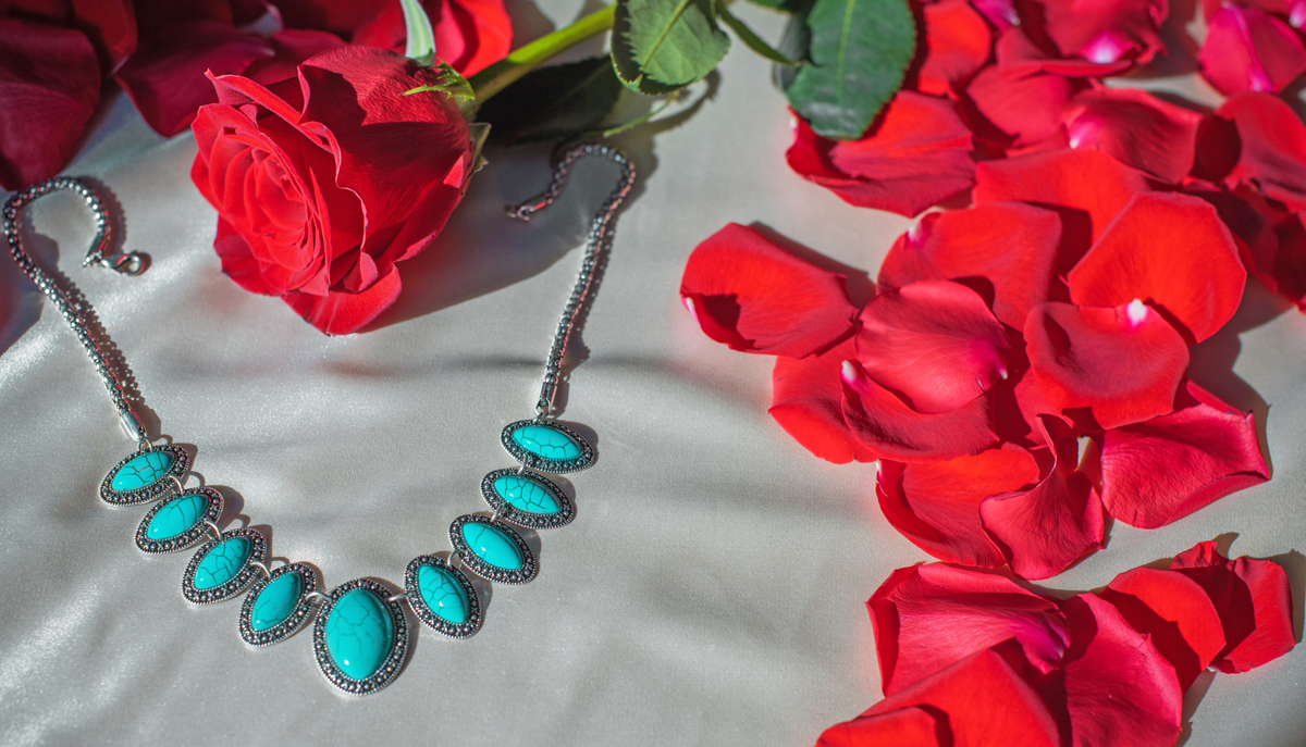 Blue stone necklace surrounded by rose pedals