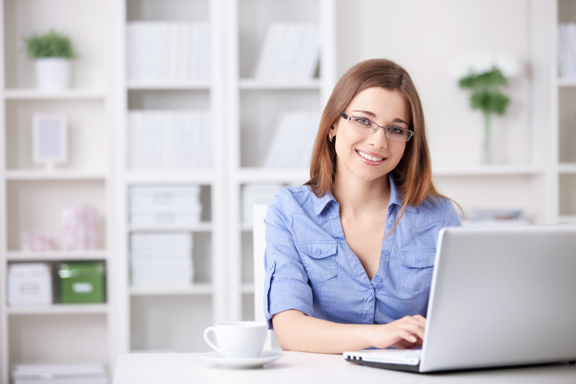 Woman on laptop smiling at the camera
